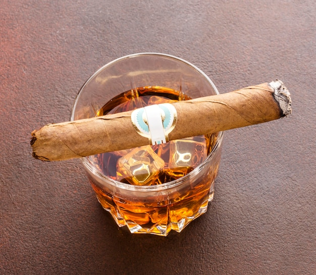 High angle whiskey with ice and cigar
