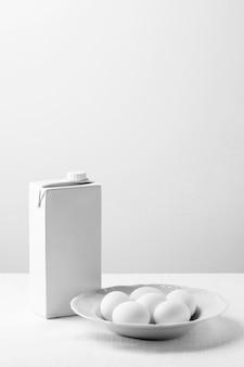 Uova di gallina bianche ad alto angolo sulla zolla con il cartone in bianco del latte