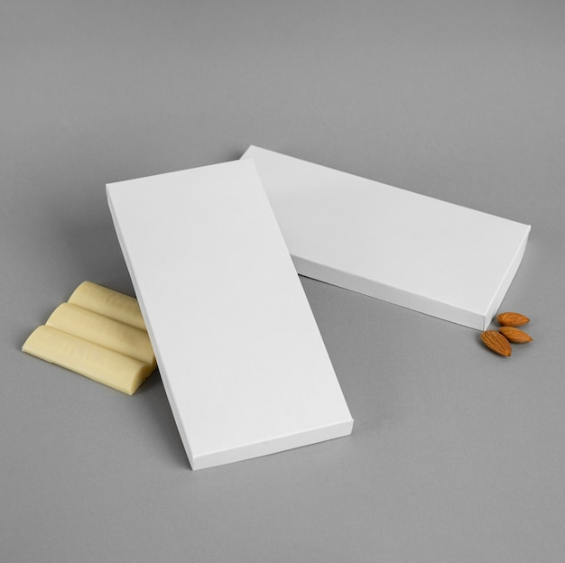 High angle of white chocolate bar with packaging and nuts