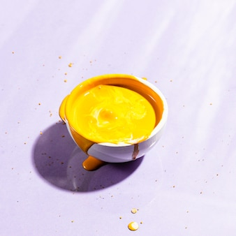 High angle white cup with yellow paint