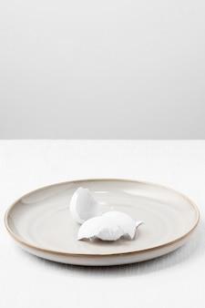 Высокий угол белой яичной скорлупы на тарелке