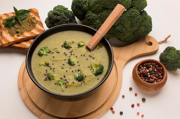 Alto angolo di zuppa di broccoli invernali nella ciotola con cucchiaio e pane tostato