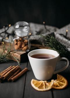 Зимний напиток под высоким углом в чашке с палочками корицы