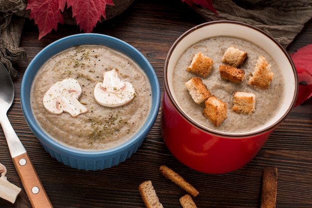 High angle of winter mushroom soup in mug and bowl with croutons