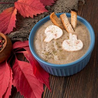 Alto angolo di zuppa di funghi invernali con crostini di pane nella ciotola