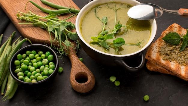 Alto angolo di zuppa di piselli invernali nella ciotola con pane tostato e cucchiaio