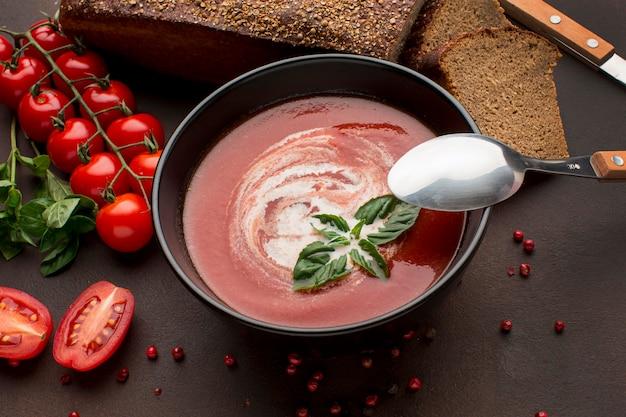 Alto angolo di zuppa di pomodoro invernale nella ciotola con pane tostato e cucchiaio