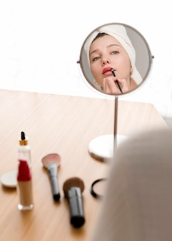 High angle woman applying lipstick
