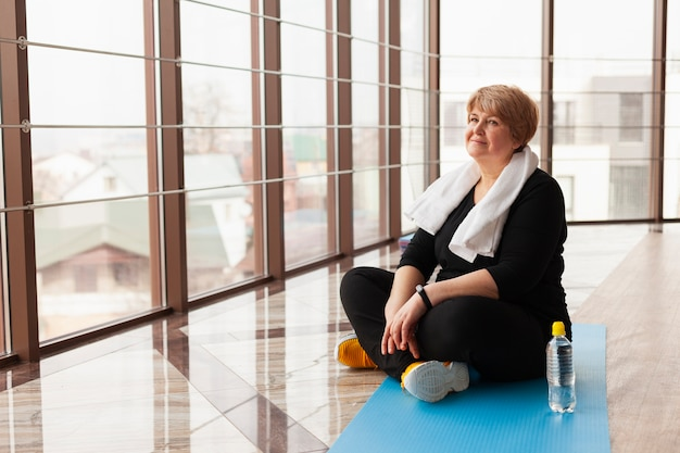 Женщина высокого угла на отдыхать спортзала