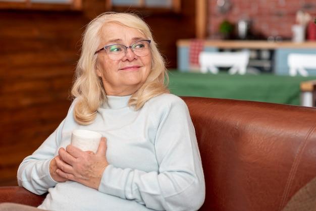Женщина высокого угла дома пьет чай