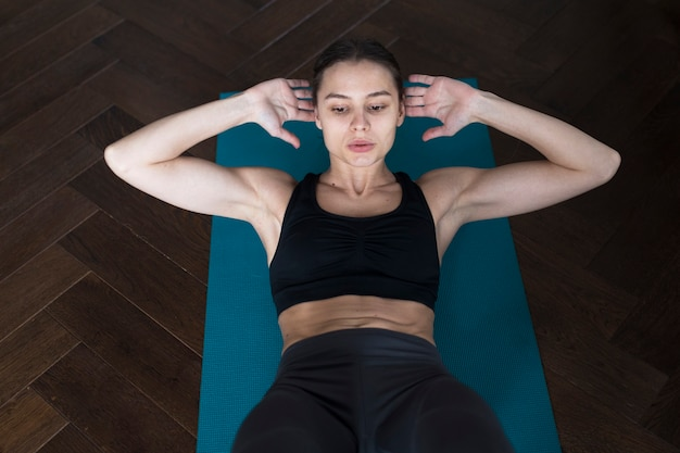 High angle of woman in athleisure doing crunches