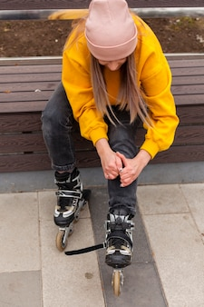 High angle of woman in beanie adjusting roller blades