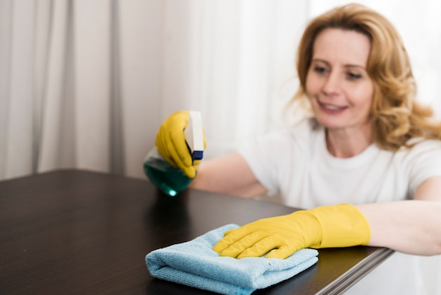 High angle of woman cleaning the table