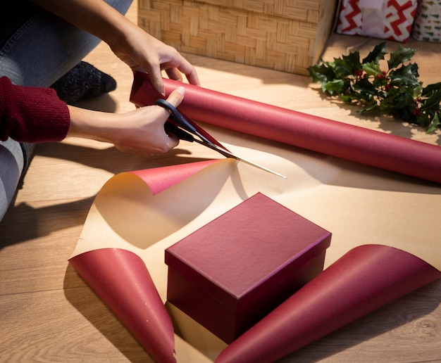 High angle woman cutting paper to wrap gifts