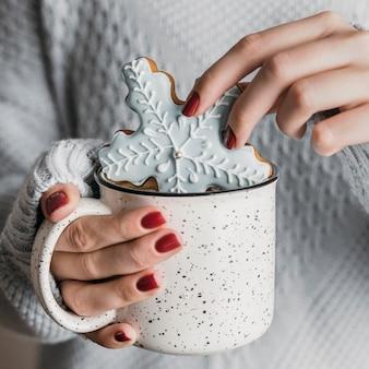 Женщина под высоким углом окунает печенье в виде снежинки в горячий напиток
