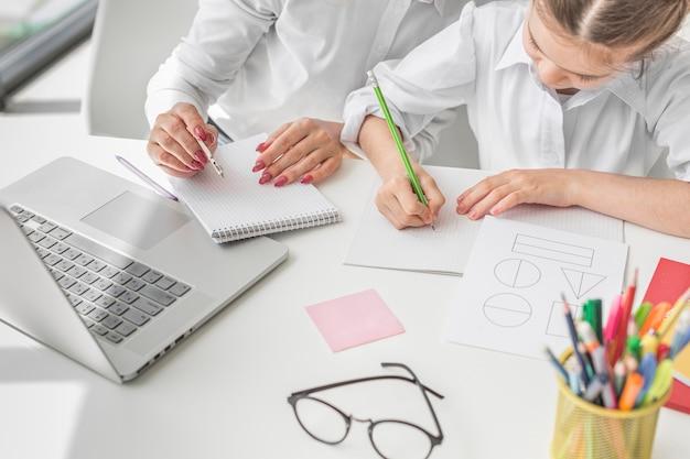 Женщина высокого угла, делающая уроки с маленькой девочкой дома