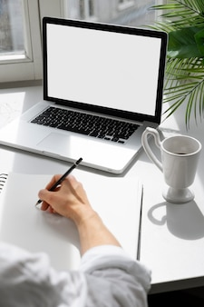 High angle of woman drawing at desk with laptop