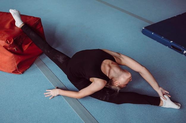 Женщина с высоким углом, тренирующаяся на олимпийских играх по гимнастике