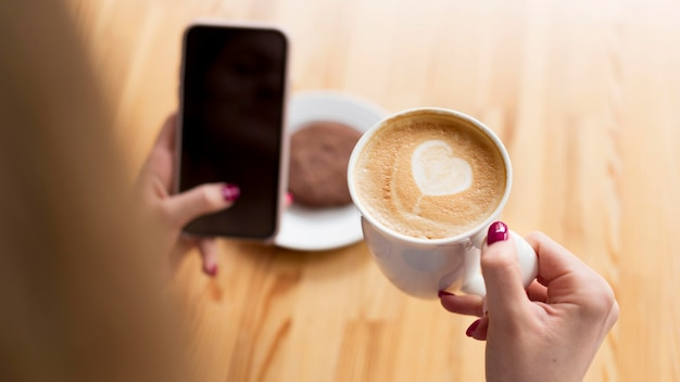 High angle of woman having coffee while holding smartphone