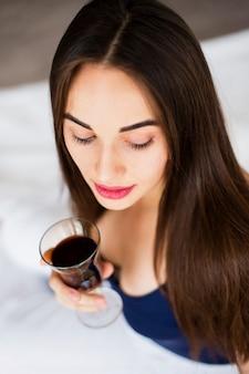 Женщина высокого угла имея бокал вина