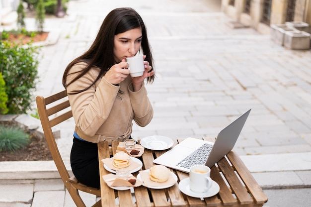 High angle of woman having lunch and working outdoors