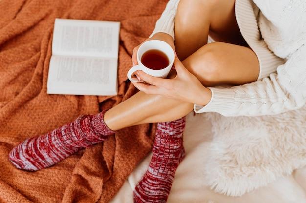 Высокий угол женщина, держащая чашку чая
