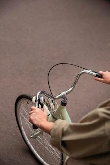 High angle of woman holding bicycle's handlebars