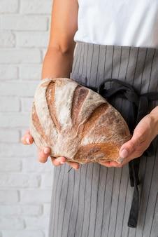 Высокий угол женщина, держащая буханку хлеба