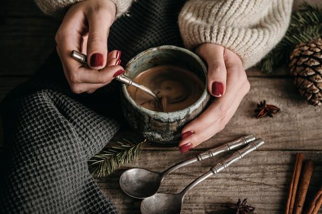 Женщина под высоким углом держит кружку с горячим шоколадом