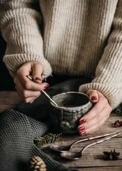 Женщина под высоким углом держит кружку с горячим какао