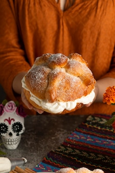 High angle of woman holding pan de muerto with cream
