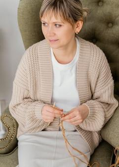 Donna di alto angolo che lavora a maglia all'interno