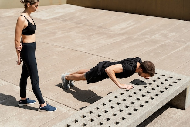 High angle of woman and man doing push-ups outdoors