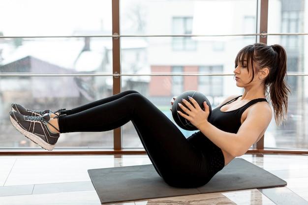 Женщина высокого угла на тренировке циновки