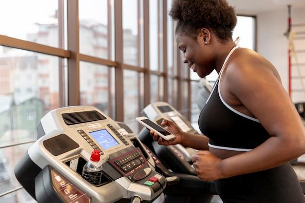Высокий угол женщина на беговой дорожке с помощью мобильного телефона