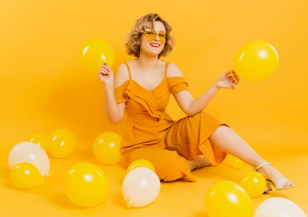 High angle woman playing with balloons