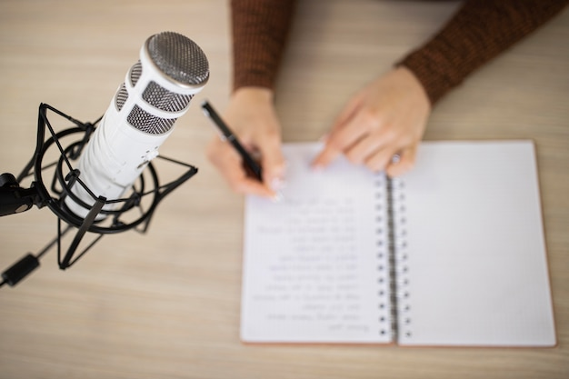 High angle of woman in a radio studio with notebook and microphone