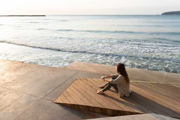 High angle woman relaxing next to the beach