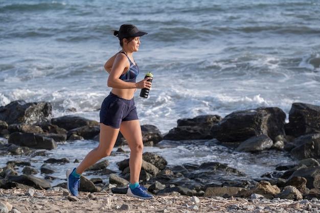 Женщина под высоким углом работает на берегу моря