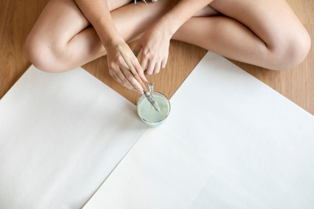 High angle woman sitting on the floor with paint