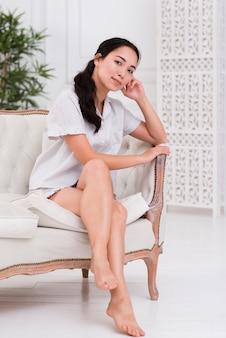 Высокий угол женщина сидит на диване