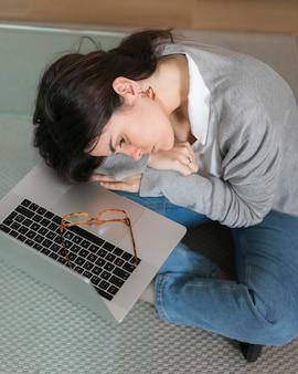 Высокий угол женщина sleepig на стеклянном столе возле ноутбука