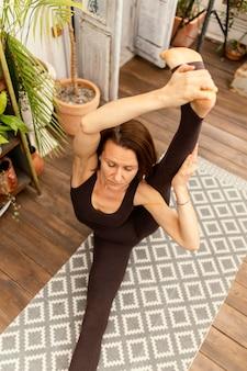 Женщина с высоким углом растяжения на коврике