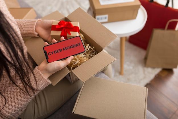 Женщина под высоким углом распаковывает пакет кибер-понедельника с копией пространства