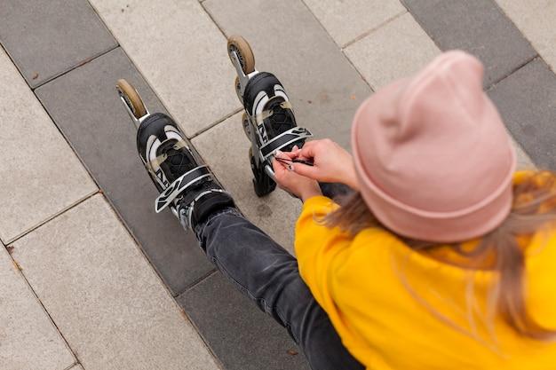 Alto angolo di donna con berretto in pattini
