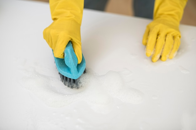 High angle of woman with cleaning gloves using brush