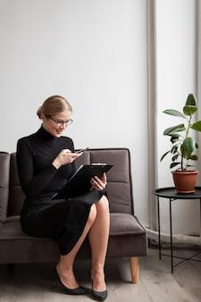 Donna dell'angolo alto con la lavagna per appunti sul divano