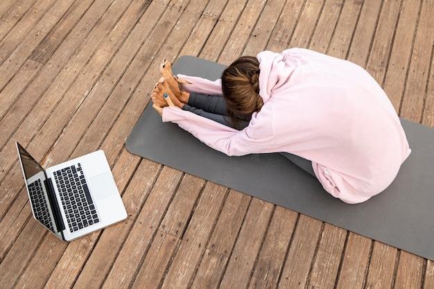 Alto angolo di donna con il computer portatile che fa yoga all'aperto