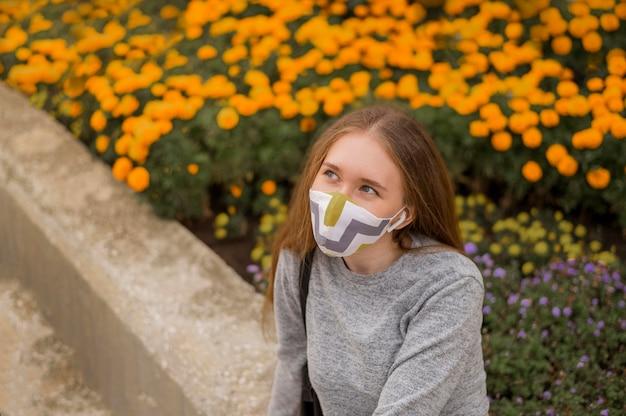 Женщина под высоким углом с медицинской маской сидит рядом с садом