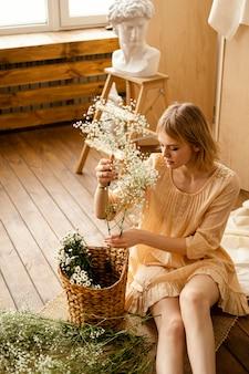Alto angolo di donna con fiori primaverili e cesto